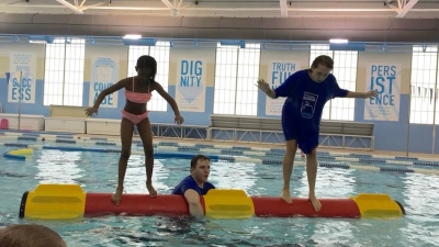 SwimRVA Camp kids balancing on a log roll